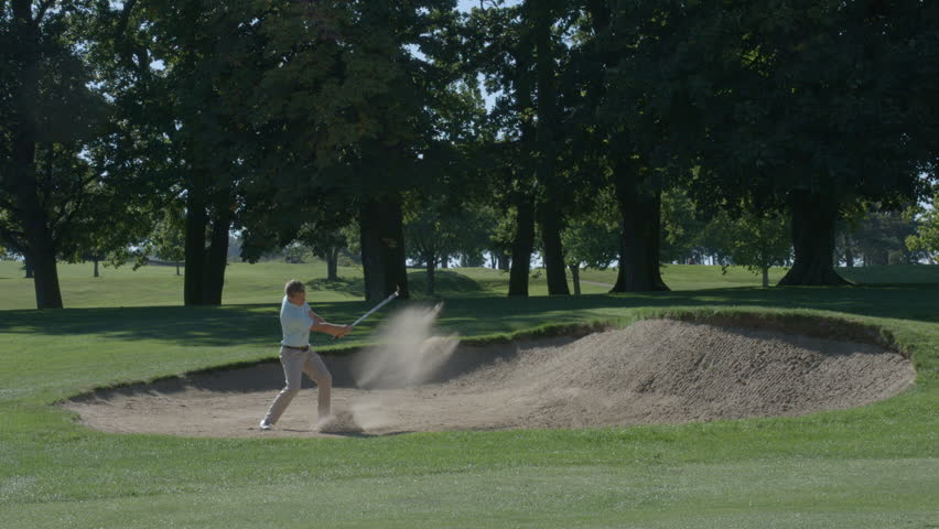 A golfer hits a ball out of a sand trap in slow motion. | Shutterstock HD Video #31429624