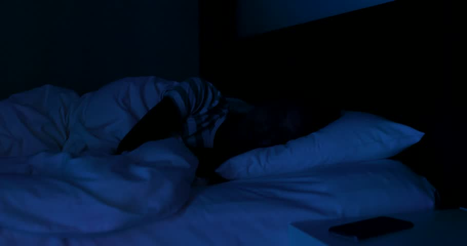 woman sleeping on bed at night and disturb by cellphone ringing 4k stock footage clip