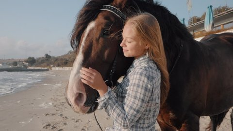Young Blonde Girl with long hair Stroking and Hugging a Horse. Slow motion. Beautiful young woman with her dark horse on seashore enjoying nature. Love and friendship concept.