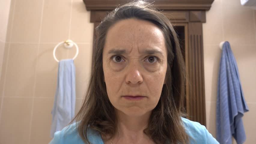 4K Funny woman peeps in her eye in mirror, bad focus
