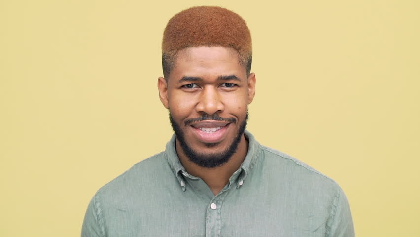 closeup dark-skinned guy with stylish haircut in blue skirt looking down then looking at camera,smiling broadly with white teeth over yellow background slow motion. Concept of emotions