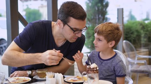 A young father tries his son's milk cocktail with ice cream and chocolate, the son laughs, the family is dining in the restaurant