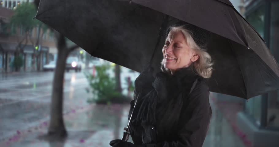 7015b4e2de67b Carefree senior woman with umbrella dancing and jumping outside in the rain  smiling. Joyful elder woman having fun outdoors on rainy day spinning with  ...