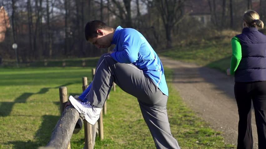 Man stretching, woman jogging in park, crane shot