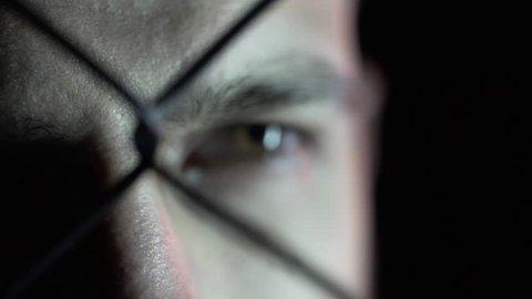 Close-up of an eye of a man behind a grid. It's a dark room.