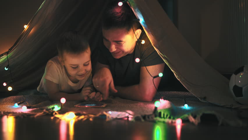 Father and son play and watching smartphone in children's room in tent with Christmas decorations   Shutterstock HD Video #31538104