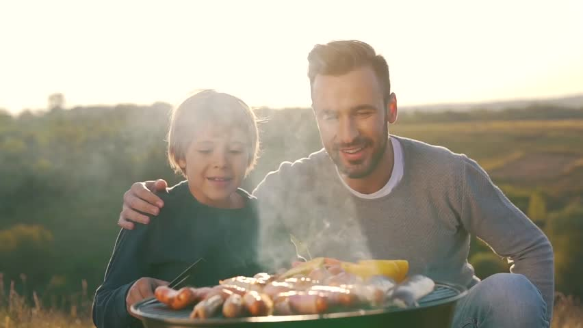 father and son cook sausages on grill.