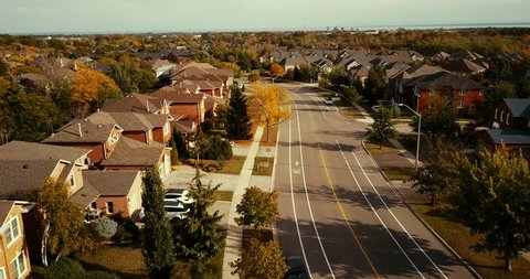 Aerial drone flight over a suburban neighbourhood in Oakville, Ontario.  Drone follows the road about 100 feet above the ground.
