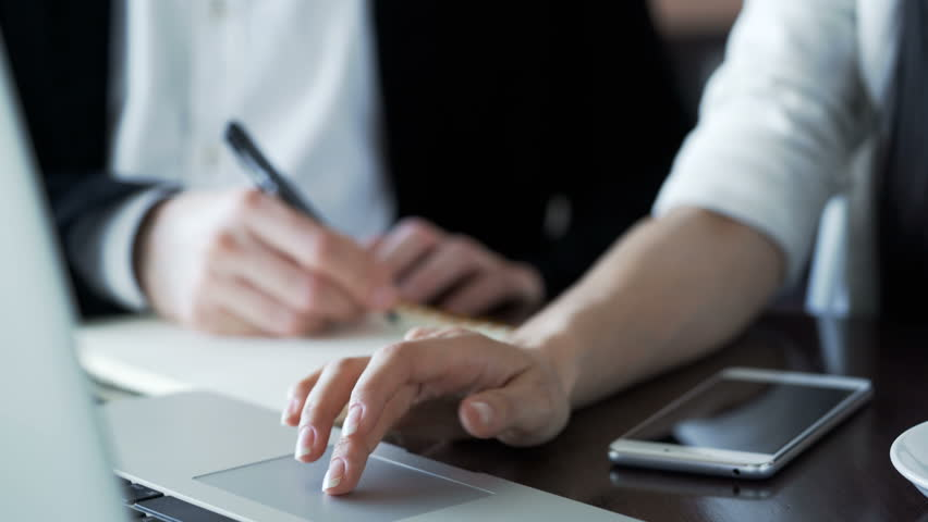 Hands of man write and woman work at pc at desk closeup. Isolated hands partners are concentrated work for job plan in workspace. Female gesture are touching touchpad and male use pen and paper | Shutterstock HD Video #31563004