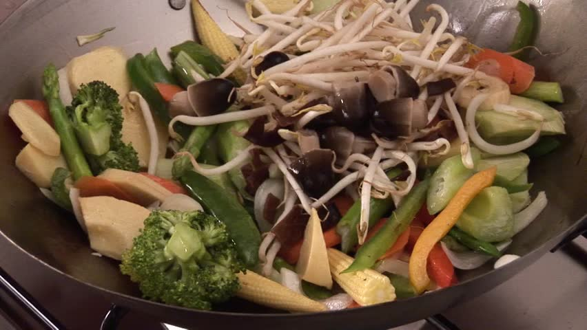 Mixing sprouts with vegetables in a wok