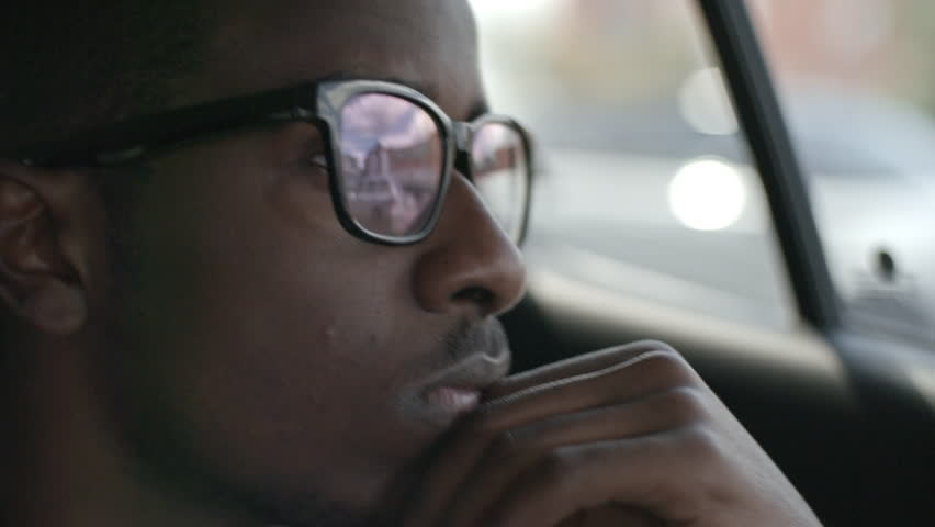 Closeup serious of African businessman in eyeglasses looking through car window while riding on backseat and holding hand under his chin