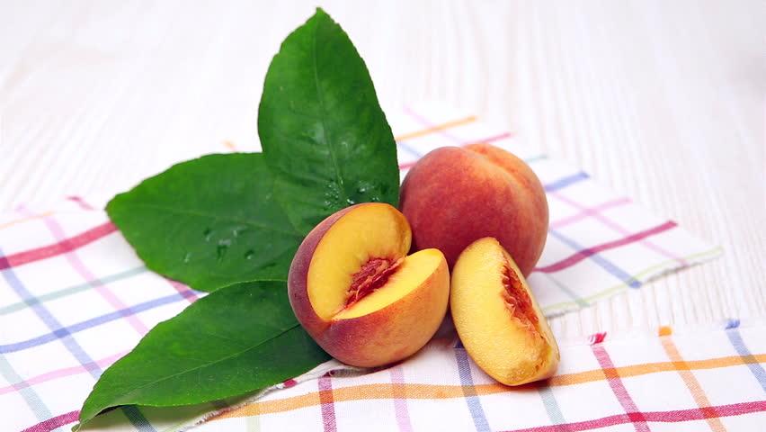 peaches, ripe peaches with a green leaf on a napkin