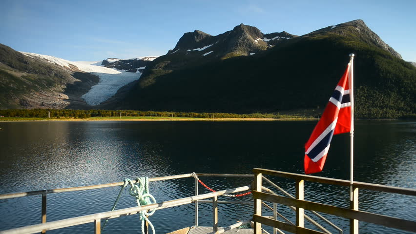 Norways flag in the harbour with Svartisen glacier in the background, Holandsfjord, Norway, Scandinavia, Europe.
