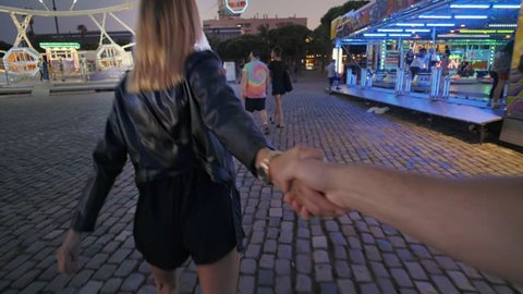Attractive pretty couple spends date night at amusement park at night, girl or young teenager holds partner or boyfriend by hand and runs towards ferris wheel attraction, have fun and enjoy love mood
