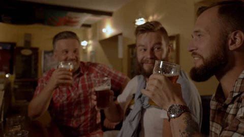 Good old friends drinking beer in a pub