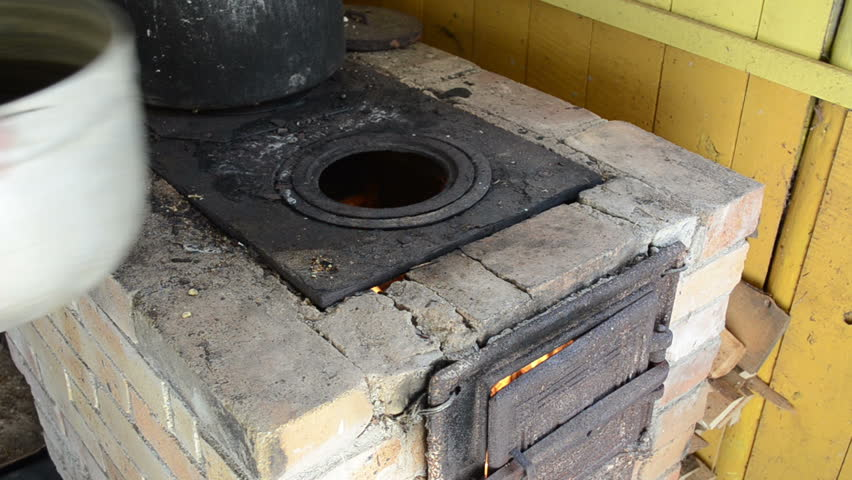 old rural kitchen furnace and firewood burning inside and hands put huge pot on it.