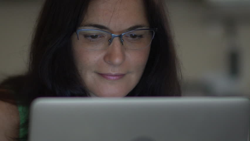 Woman in glasses smiling as she watches laptop computer closeup | Shutterstock HD Video #31596124