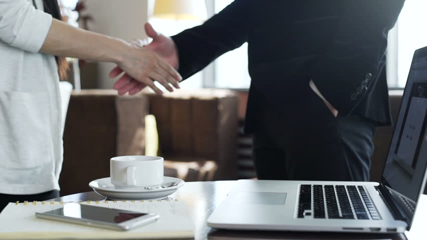 Two colleagues shake hand after negotiations closeup. Male and female success person signed a agreement between companies and congratulation deals slow motion indoors. At table laptop and documents