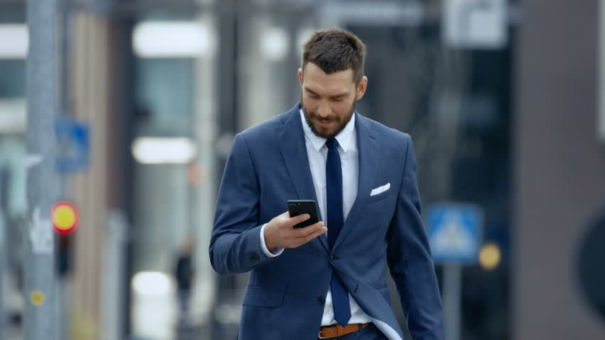Successful Business Man Uses Smartphone While Walking on the Big City Business District Street. Shot on RED EPIC-W 8K Helium Cinema Camera.