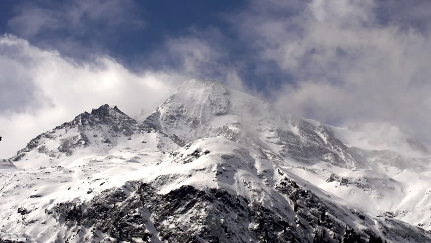 Storm clouds and high winds race across high mountains and glaciers.   Shutterstock HD Video #31601824