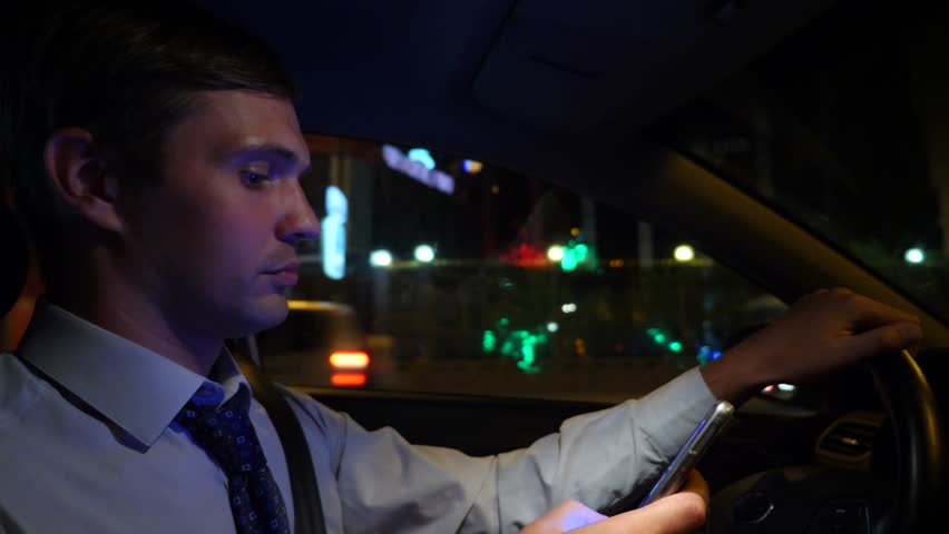Texting with a smart phone in car. a young businessman is driving a car around the night city and uses his smartphone. 4k, slow motion