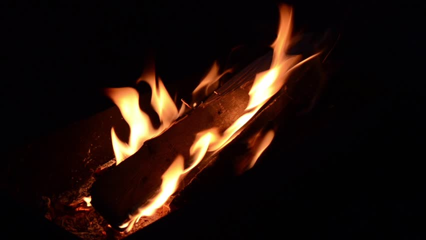 Fire burning in outdoor pit at night.