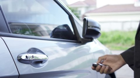 Woman press the remote to unlock the car and open the door.