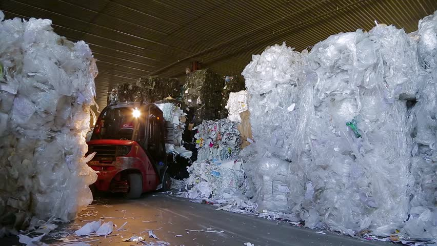 Loader sorts the pallets with the recycled material at the waste processing plant. Warehouses with recyclable materials at the garbage processing factory. Footage with sound.