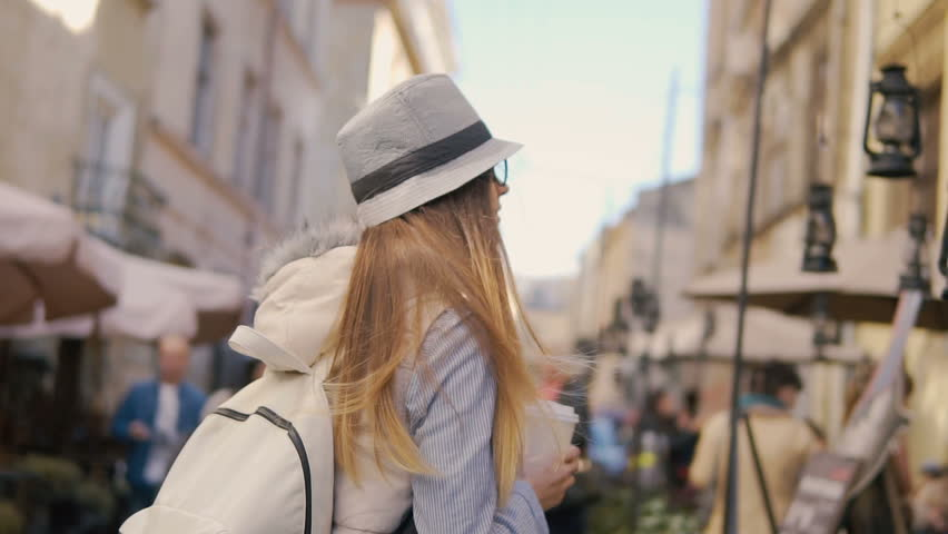 Relaxed caucasian girl, in striped hat and glasses, holding coffee while walking in the street, sunny day, slowmotion | Shutterstock HD Video #31709494