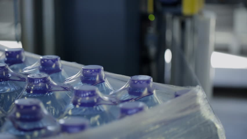 Process of packaging plastic bottles with water on conveyor belt in factory. Flasks rotate on automatic line and are packed in thermoresistant paper in workshop of modern enterprise. Newest equipment | Shutterstock HD Video #31710805