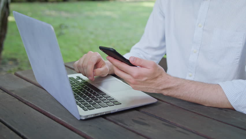 A young man's hands using a laptop and a phone in the park. Closeup shot. Soft Focus | Shutterstock HD Video #31734304