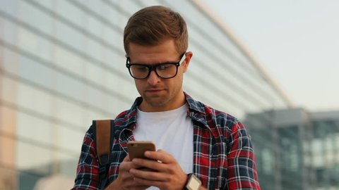 Closeup. Portrait of a happy young man walking in the city. Wearing glasses and surfing his phone. Blurred background.