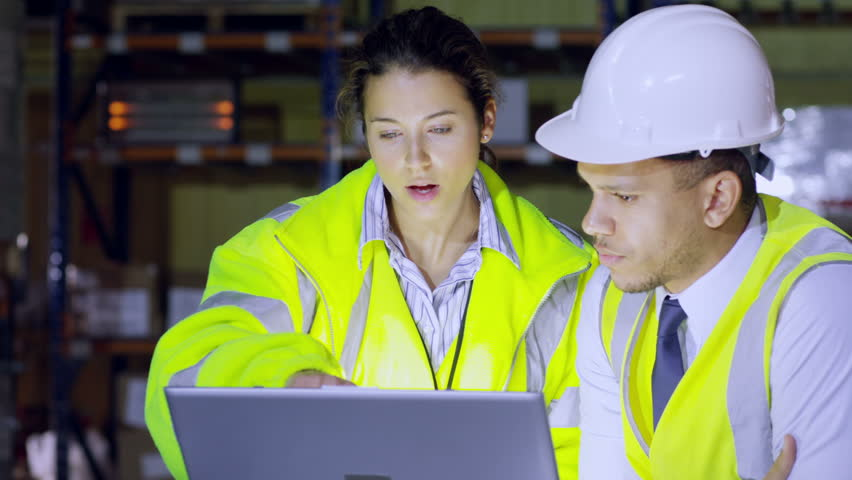 One male and one female warehouse manager are discussing their business and looking at a laptop computer. In slow motion. | Shutterstock HD Video #3175243