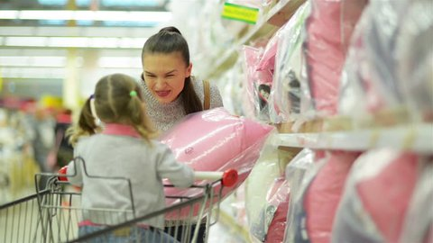 Pretty Beautiful Mother with Dark Hair is Showing Pink Pillow for Her Daughter Standing near Supermarket Shelf with Bedclothes. Little Girl with Two Ponytails is Sitting in Shoping Cart.