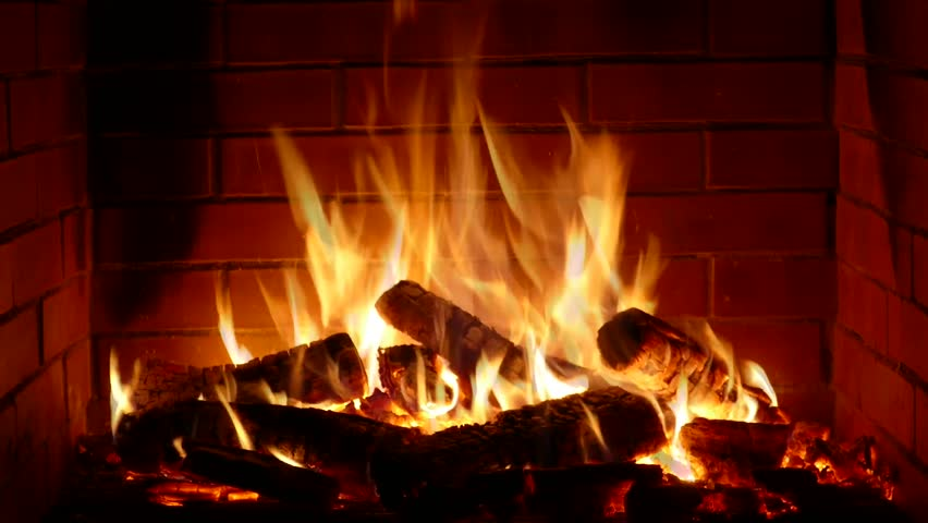 Wonderful satisfying close up shot of wood burning slowly with orange fire flame in cozy brickwork fireplace atmosphere