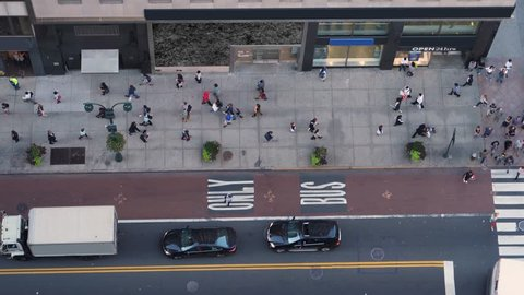 A high angle view of pedestrians and traffic on 5th Avenue in midtown Manhattan.
