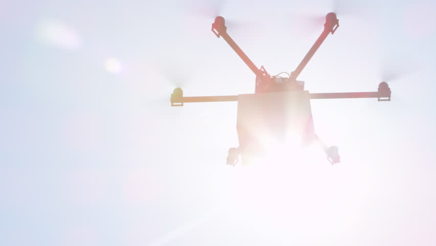 CLOSE UP LENS FLARE: UAV drone delivery. Multicopter flying brown package over sun. Drone delivering goods to your home. Futuristic shipment by helicopter drone. Multirotor logistics and transport