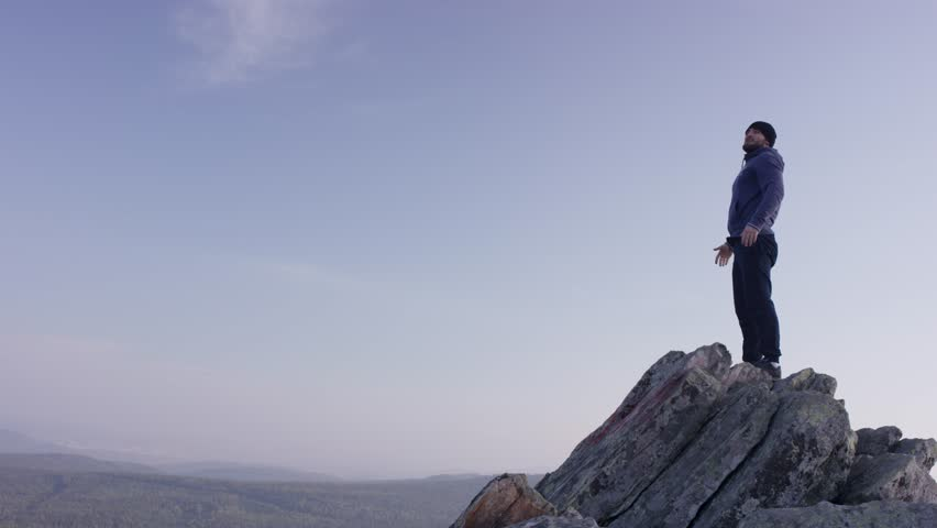 Man on top of the mountain. A young, athletic man stands on a high rock | Shutterstock HD Video #31830754
