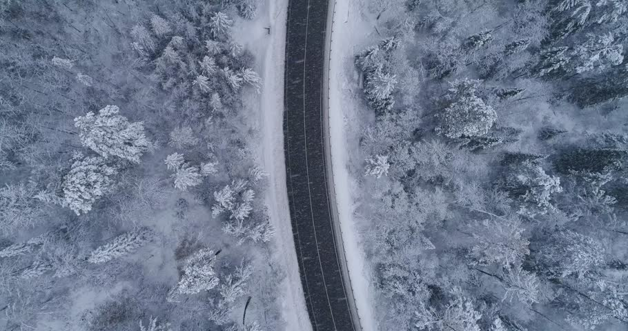 Road in the winter forest. Heavy snowfall. Aerial View.