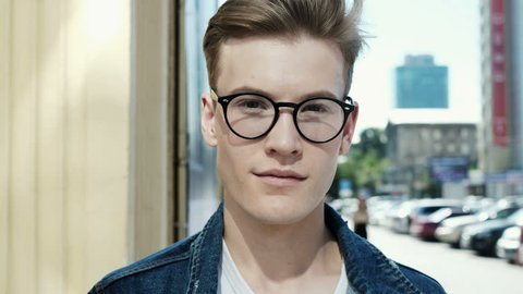 Portrait of happy cute caucasian man smiling in city. Close-up. Handsome young man with glasses looking at camera and smiling
