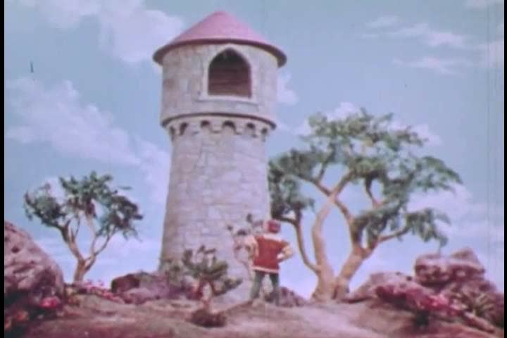 CIRCA 1950s - A Prince watches a witch climb the side of a tower using the captive Rapunzels hair, in an animated fairy tale, in 1951.