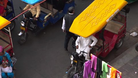 Graded & ungraded: Colorful Indian rickshaw in busy congested road traffic street in India Asia - Slow motion wide aerial birds-eye view