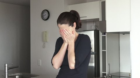 An upset adult woman in her thirties (30s) in her home kitchen crying. Woman concept (slider motion) copy space