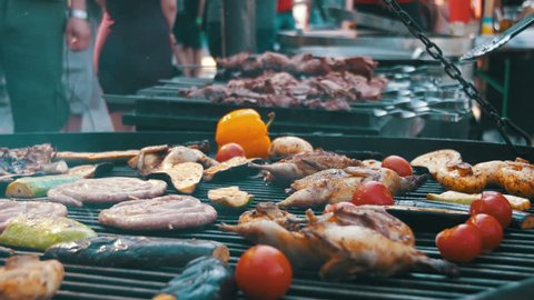 Cooking of Meat and Vegetables on the Grill. Hand Using Tongs For Turning Meat on the Barbecue. Sausages, chicken, bell pepper, eggplant, tomatoes are fried on a barbecue. Outdoor cooking.