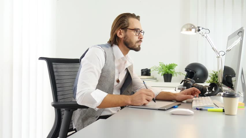 Male photographer editing photography in office with computer, camera and graphic tablet  | Shutterstock HD Video #31888774