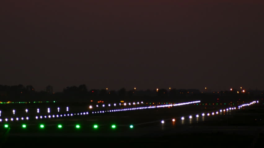 Big plane landing at Barcelona airport seen from behind at night with lit signal lights on the runway.