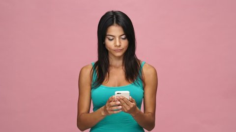 Shocked happy brunette casual woman using smartphone and showing thumb up isolated over pink