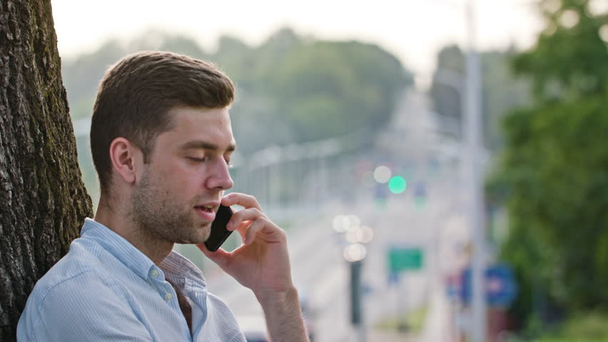 A young man talking on the mobile and sitting under the tree. Medium shot. Soft focus.   Shutterstock HD Video #31917214