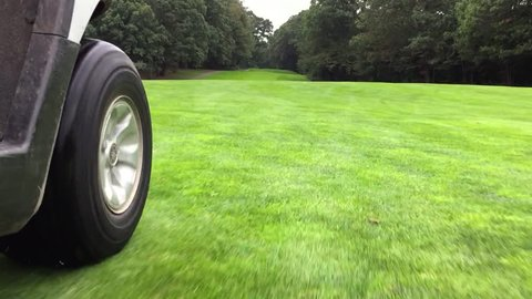 Golf cart driving down fairway on a beautiful golf course during summer day time. Low angle POV driving plate point of view to wheels rolling on grass