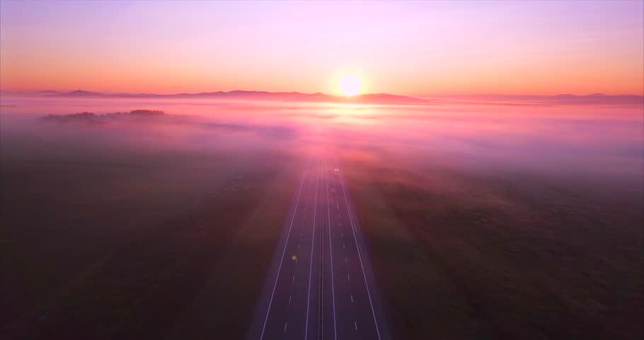 Amazing aerial view of the road with driving cars, morning fields and forests covered with fog and red rising sun. Russia
